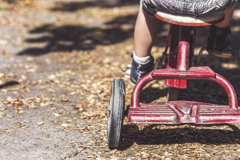 niño jugando con triciclo