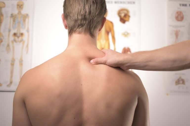 hombre sentado de espalda en consultorio quiropractico